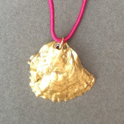 Gold oyster pendant with fuchsia cord